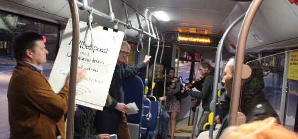 Photo inside of a night bus with a musician, violinists and poets.